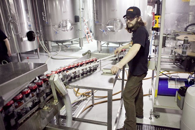 Paul Stelmach of Surly Brewing Company watches the production line of the canning process Wednesday afternoon in the warehouse in Brooklyn Center.
