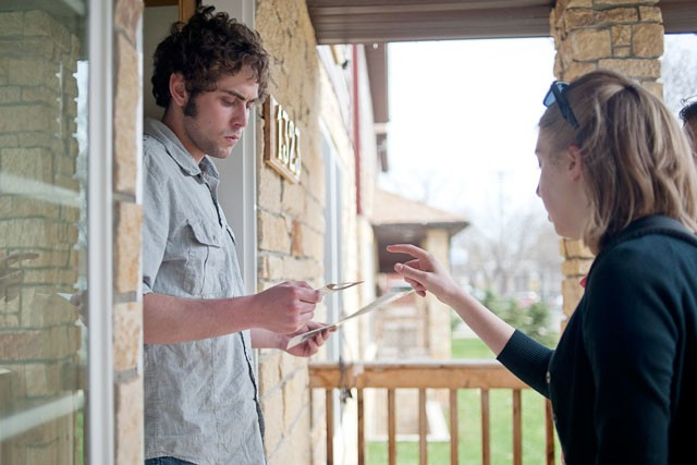 Student Neighborhood Liaison Carrie Noble distributes literature to Marcy Holmes resident junior Nick Buchner Monday afternoon.  The group went door to door in Marcy Holmes and SE Como neighborhoods with representatives from city inspections and police to inform residents about recent ordinances and resources available to them through the city.