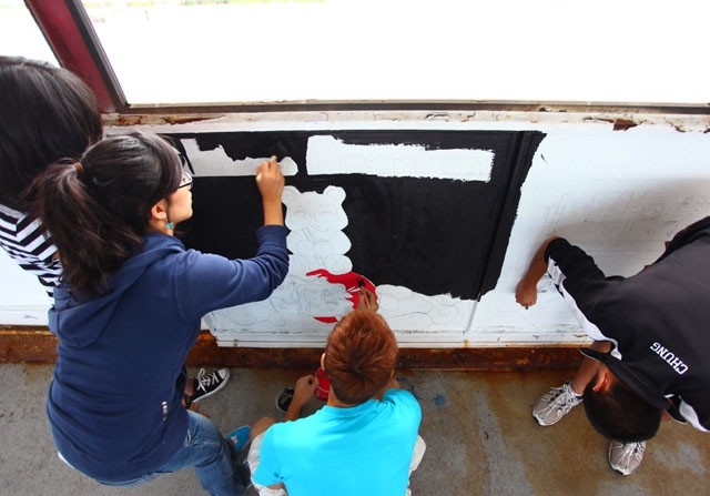 Members of the Chinese American Student Association paint a mural on the Washington Avenue Bridge on September 9th. Due to the safety conditions of light rail construction, the famous Paint the Bridge may not happen next fall.