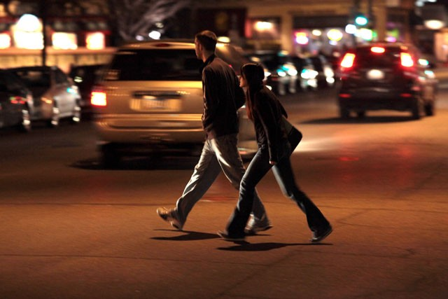 Pedestrians cross Washington Ave in the Stadium Village area Friday night. The University Police Department is increasing the number of citations given to pedestrians disobeying traffic signals.