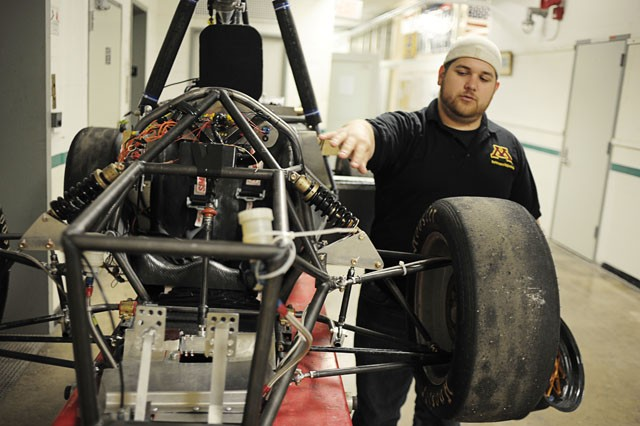 Formula SAE president Thomas Kornblum explains the new suspension on their car Wednesday in the Mechanical Engineering Building.