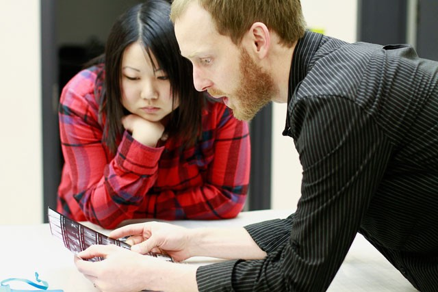 Graduate student and TA Andy Mattern helps psychology senior Tara Wong review her contact sheet Monday in Regis' photo lab.