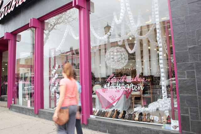 People walk past the window displays in front of Heartbreaker on Saturday in Uptown. The displays were designed by University students.