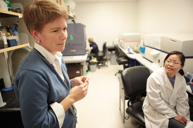 Professor of Immunology Kristin Hogquist talks to a graduate student in her lab, which is attached to her husband's, Tuesday in the Wallin Medical Biosciences Building. Hogquist said the University hasn't paid close enough attention to gender equity in salaries.