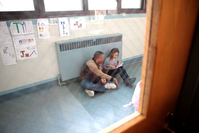 Phil Binns helps Lilia Torchia-Stately finish her MCA practice test in the hall of Southside Family Charter School.