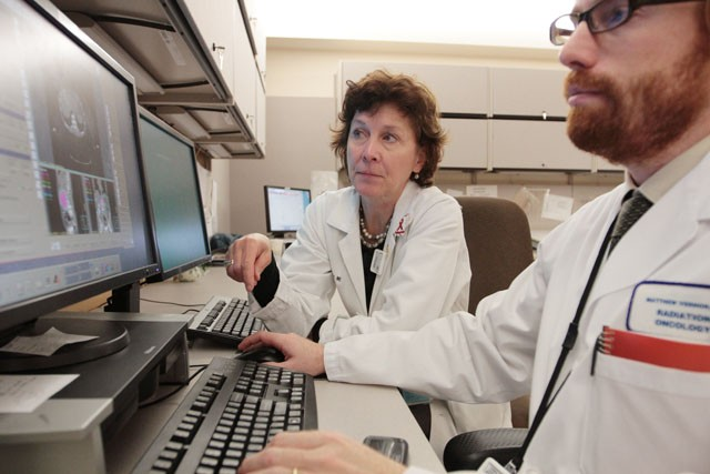 Kathryn Dusenbery, head of therapeutic radiology, works with medical resident Matthew Vernon on Monday at the Masonic Cancer Center.  Dusenbery is one of three female department heads at the Medical School.