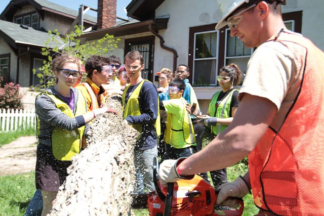 Student volunteers work together to clean up fallen trees on Thursday in North Minneapolis.