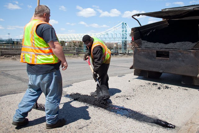 Workers Bob Lucky, left, and Andre Johnson, right, fill a pothole with hot asphalt on Tuesday in Minneapolis.