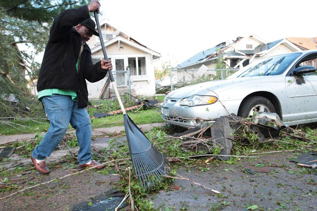 Charles Donald clears glass and debris from the road Sunday hours after a tornado tore past his house in North Minneapolis.