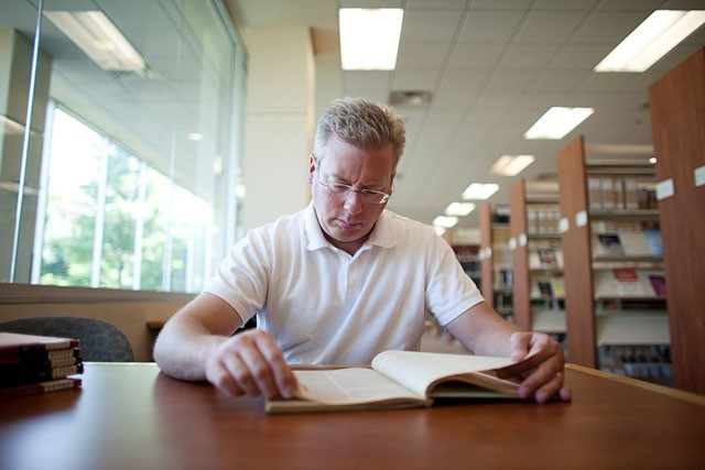 Pastor David Kind spends hours going through district documents Monday in the Concordia University Library. Kind tries to gather all the documents to convince the district not to sell the property to the campus ministry.