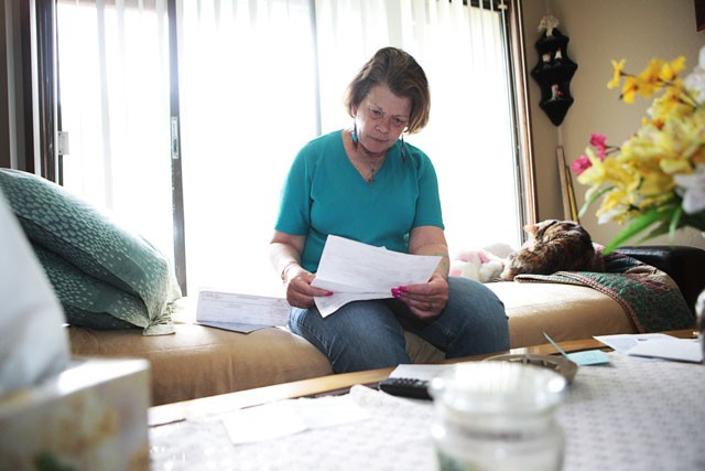 Pat Tschida looks through her bills from the Universtiy dental clinic Thursday morning in her apartment in St Paul. The University dental clinic accepts state funded insurance like Minnesota Care which allows Tschida to get less expensive dental work done.