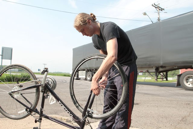 Graduate student Marcus Beck removes a wheel Friday during a pit stop North of Willmar, Minn.