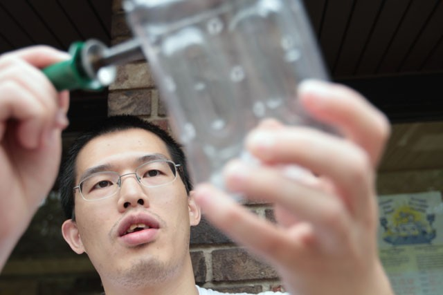 Graduate student Yi Zhang pokes holes in a bottle with a soldering iron Saturday at Van Cleve Park.  The perforated bottles collect and distribute water throughout the soil.