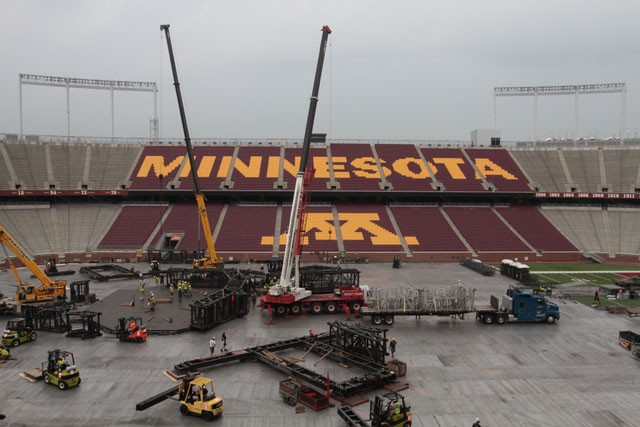 Workers try to beat the rain Tuesday while building the stage for the upcoming U2 concert at TCF Bank Stadium.