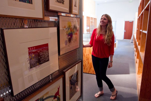 Katie Covey, Weisman Art Museum employee and a recent University of Minnesota graduate, showcases art available for rent to students and employees at the Weisman on Monday.