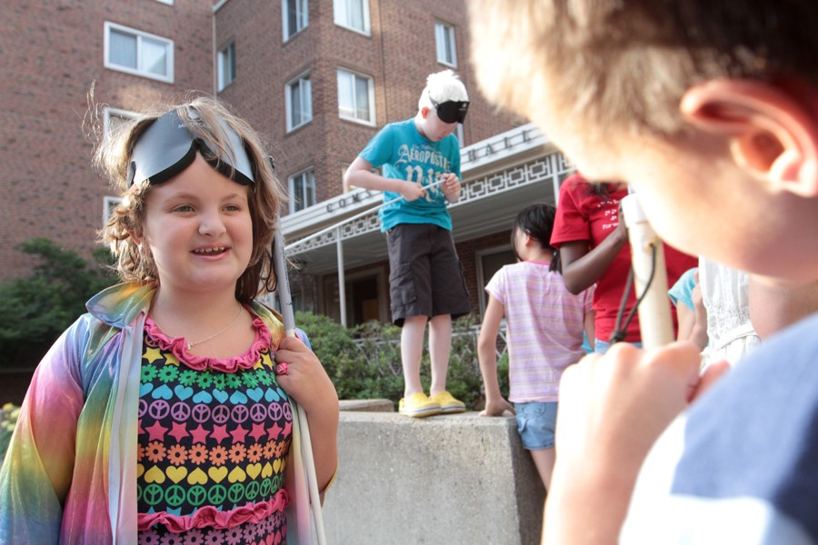 Anna Walker, left, speaks with Brandon Pickle Thursday outside Comstock Hall.  The children spent the day with The Buddy Program, which is designed to teach blind children useful techniques  for navigating the world.
