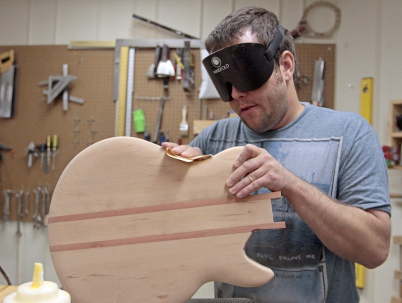 Brice Lennes sands down a guitar Thursday that he made by hand at the Pillsbury Mansion in South Minneapolis.  Lennes wears a blinder in order to work without relying on the little vision he has left.
