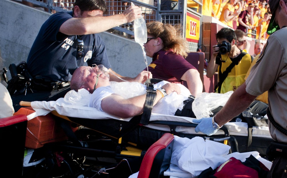Minnesota head coach Jerry Kill is rushed off the field after collapsing with 20 seconds to go in the fourth quarter on Saturday at TCF Bank.