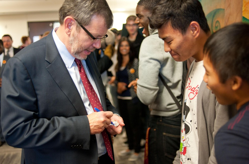 University President Eric Kaler signs buttons while visiting the second floor cultural centers Thursday in Coffman Union.