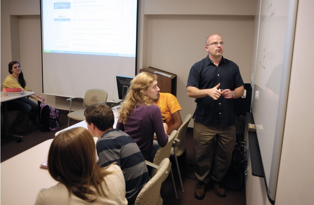 School of Nursing associate professor Joe Gaugler leads his freshman seminar on chronic diseases on Tuesday in Weaver-Densford Hall.  The course is the only freshman seminar offered by the Academic Health Center.
