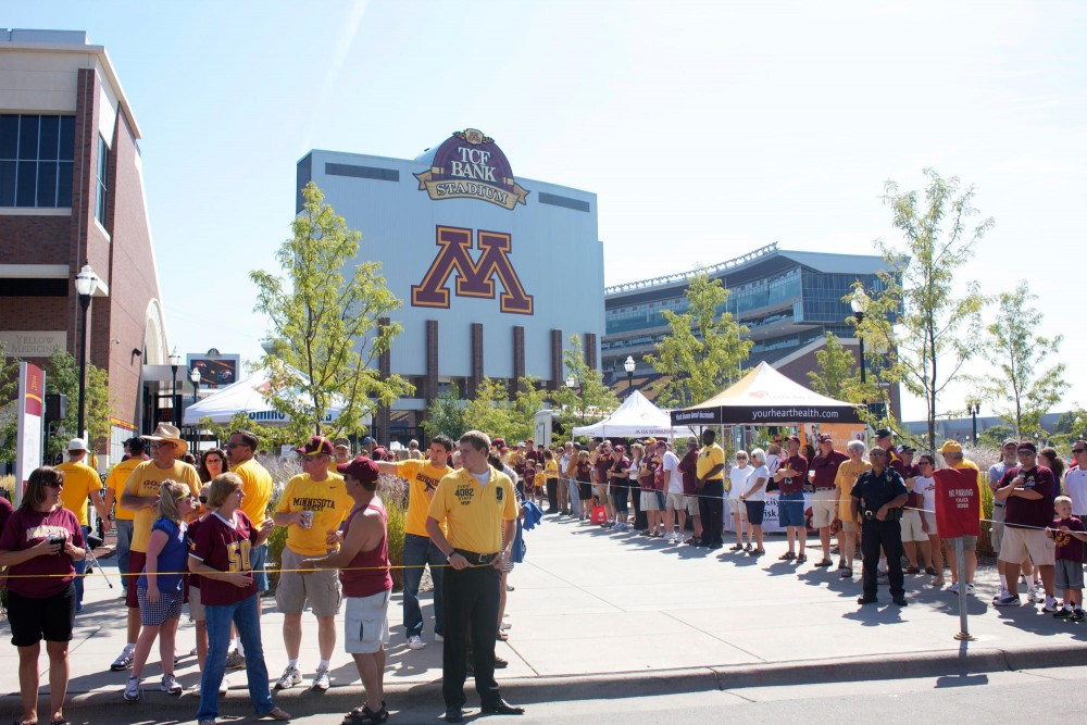 Students, families and alumni wait patiently for the U of M Marching Band and cheerleaders to arrive at TCF Stadium for the first home football game of the season.