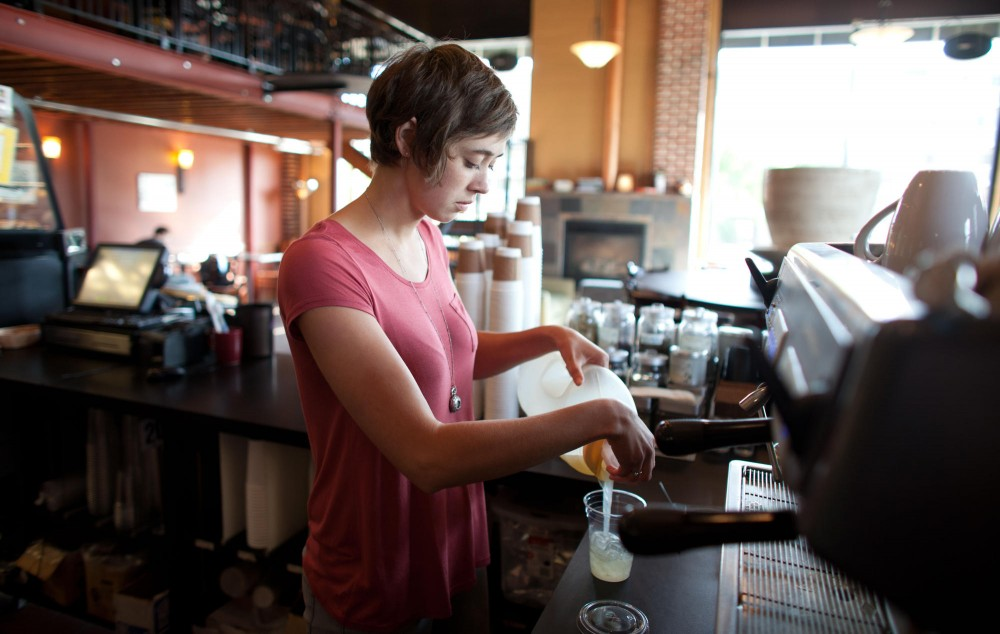 Junior Emily Neighbors pours a lemonade for a customer Tuesday at Overflow Cafe on University Ave.