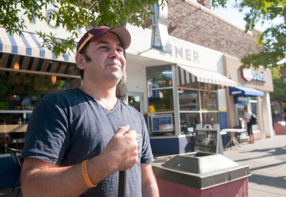 Tony Nicklow takes a break from sweeping in front of his restaurant, Tony's Diner, Wednesday in Dinkytown.
