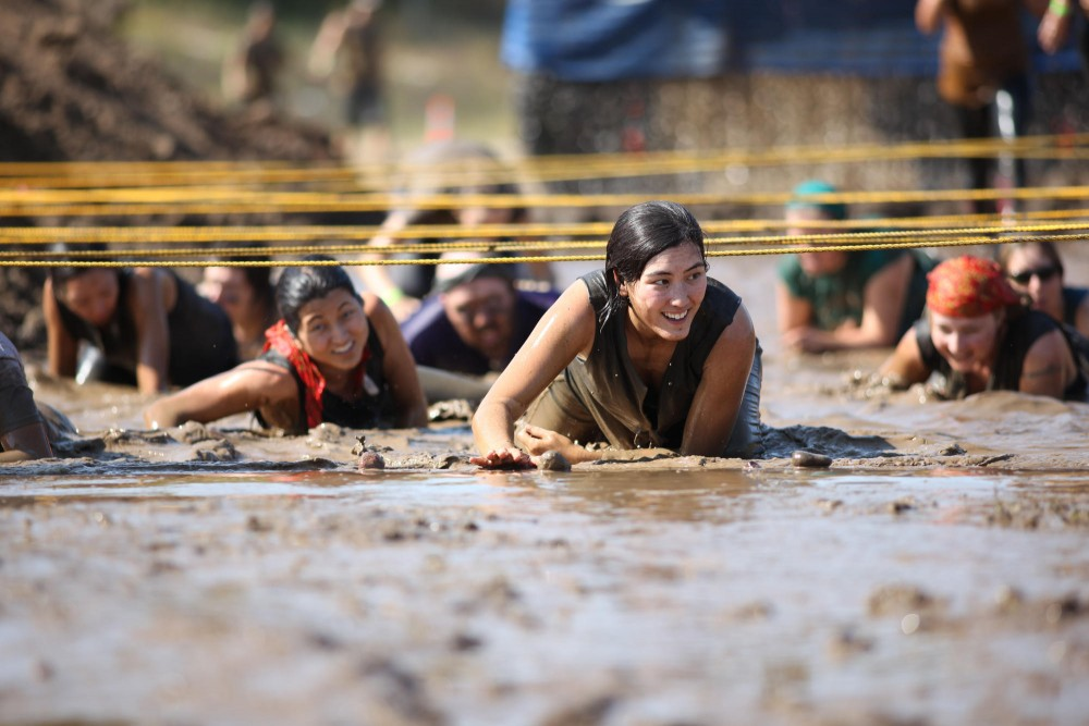 Participants in the Mud Run MS Twin Cities crawl through the last obstacle in the 10k obstacle course Saturday afternoon at the Trollhaugen Ski Resort in Dresser Wisconsin.
