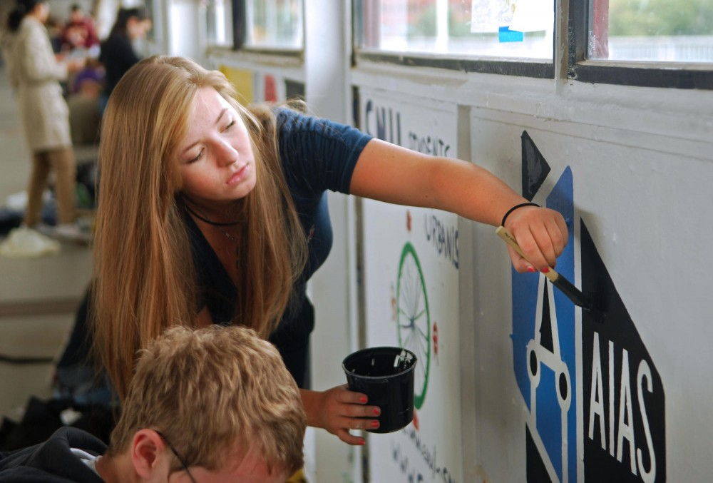 Junior Christina Kramarevsky paints a panel for the American Institute of Architecture Students of Minnesota Friday on the Washington Ave. bridge.