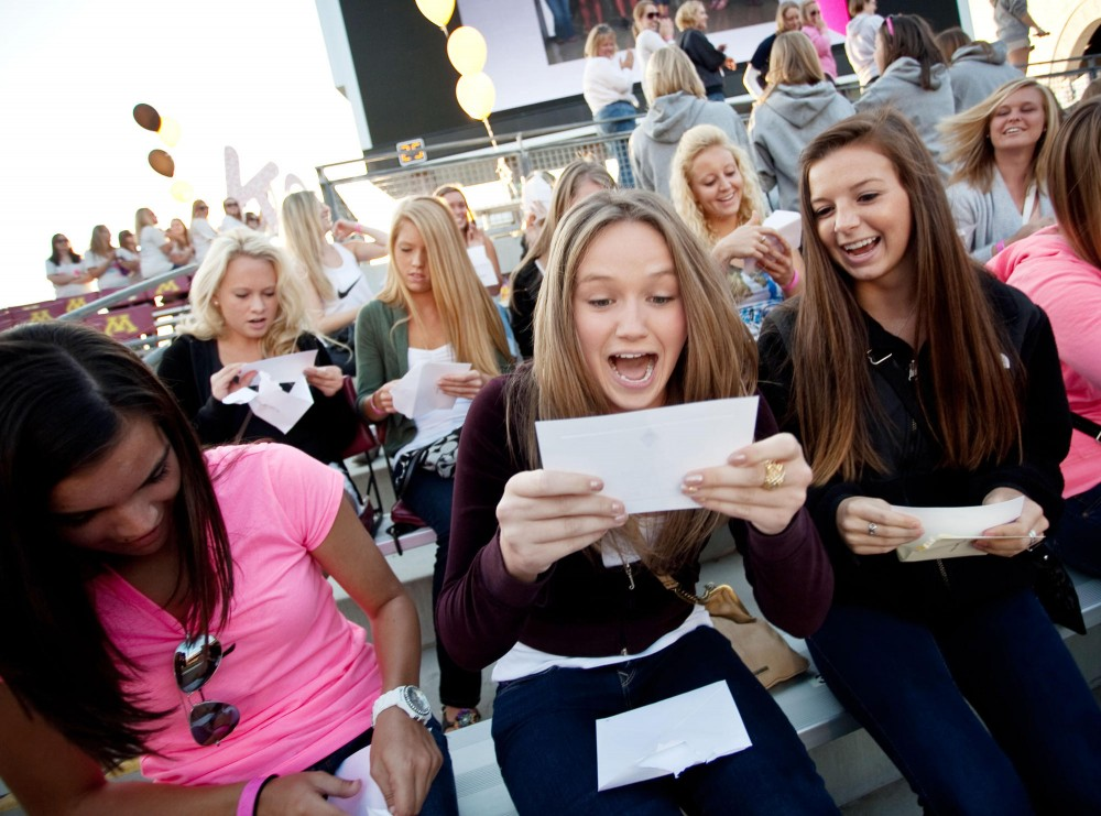 Freshman Megan Howe opens her bid envelope Tuesday afternoon at the TCF Bank Stadium. The envelope contained an invitation to join one of the sororities on campus.