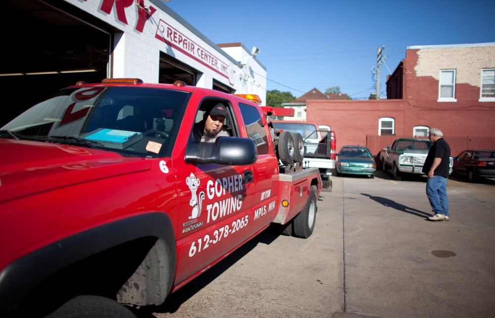 Gopher Towing tow operator Greg Chilton backs up to park the towed car in spot Tuesday at an auto shop in NE Minneapolis.