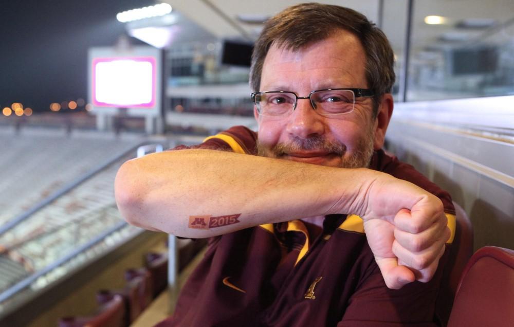 President Eric Kaler displays his temporary class of 2015 tattoo Thursday evening at TCF Bank Stadium.