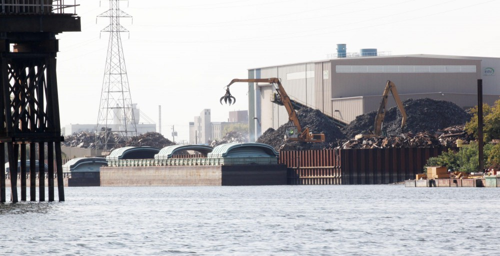Barges are loaded with scrap metal on Monday along the Mississippi Riverbank in North Minneapolis.  The area would be redeveloped into park and wetland under the plan.