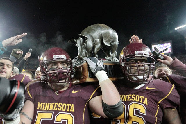 Senior D.J. Burris, left, and Junior Brandon Kirksey hold up the Floyd of Rosedale trophy after their win against the Iowa Hawkeyes on Saturday at the TCF Bank Stadium. It was the Gopher's first trophy win since 2006.
