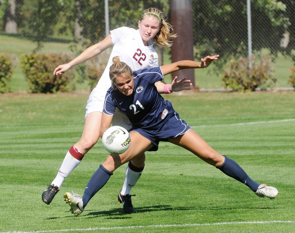 Carly Niness, no. 21 for Penn State, defends the ball against Minnesota player no. 22, Lauren Bauer at Sunday's women's soccer game in Falcon Heights.