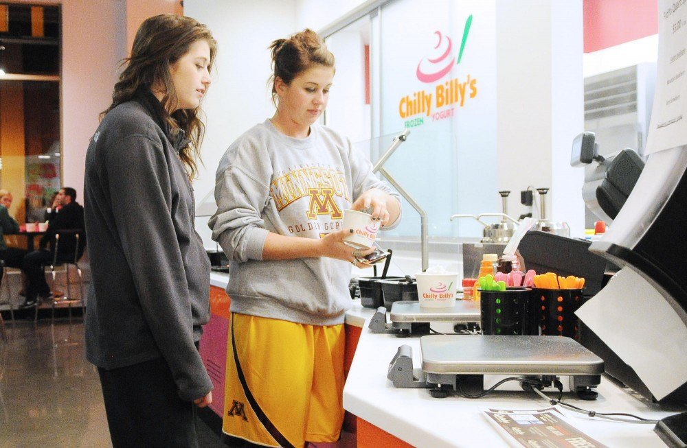 Sisters Ellen and Kaylen Larson indulge in frozen yogurt Monday night in Dinkytown. Chilly Billy's has sponsored numerous organizations and Greek communities over the past couple of months.