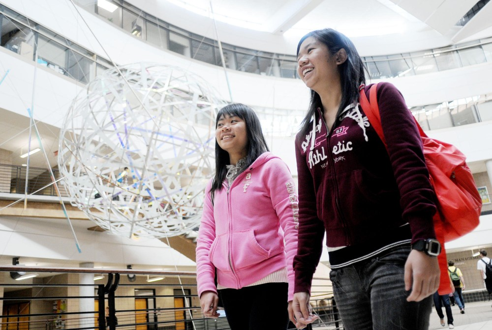 Exchange students Avida Ng and Karen Tam walk out of Carlson Monday afternoon. They're both from Hong Kong, spending a semester at the University of Minnesota to study economics and management.