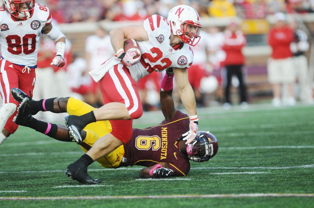 Nebraska running back Rex Burkhead applies a strait arm to Gophers defensive back Michael Carter Saturday at TCF Bank Stadium. The Huskers defeated the Gophers 41-14.