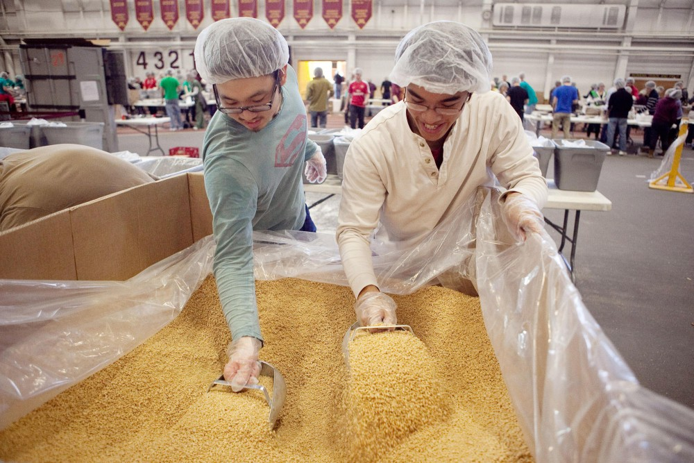 Chris Hong, left, and Jaymond Huinh, right, scoop soy into containers for other volunteers to disperse into the manna packs for Feed My Starving Children Saturday morning in the University Field House. The mobile packing event was hosted by the Pre-Med American Medical Student Association and is the first time Feed My Starving Children has been on campus.