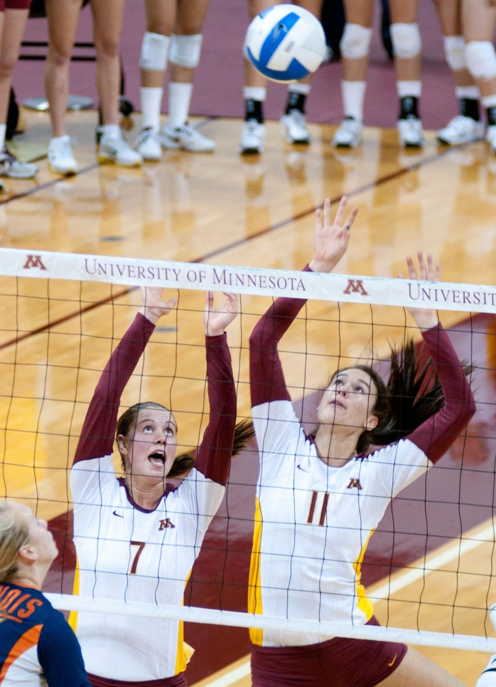 Ariana Filho and Mia Tabberson block the ball while playing against Illinois Friday night in the Sports Pavilion.