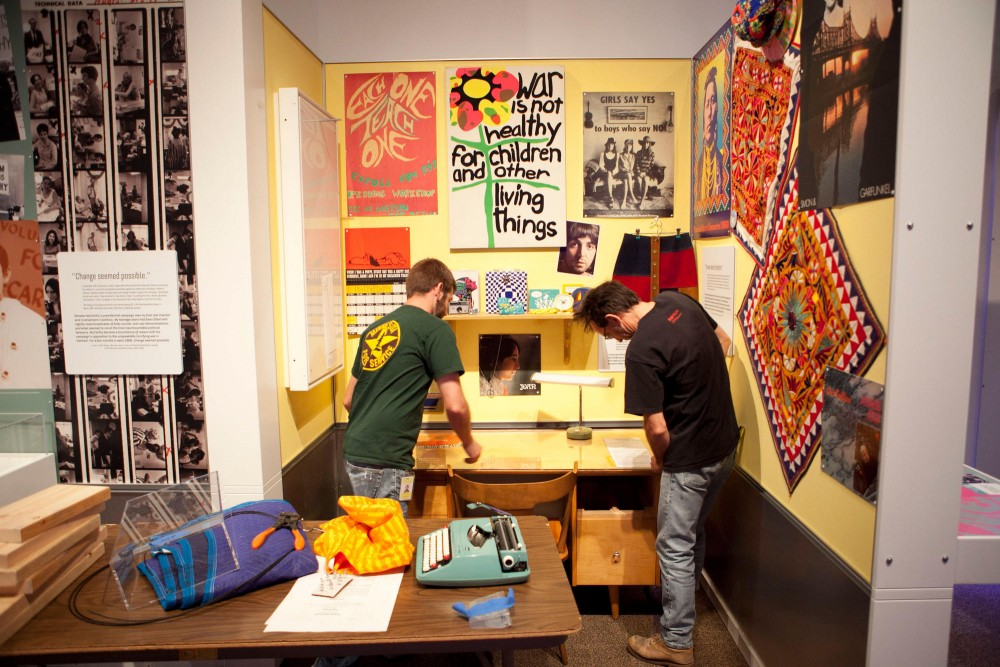Workers for the Minnesota History Museum work on a display of a typical 1968 dorm room Friday morning. The display has artifacts from the