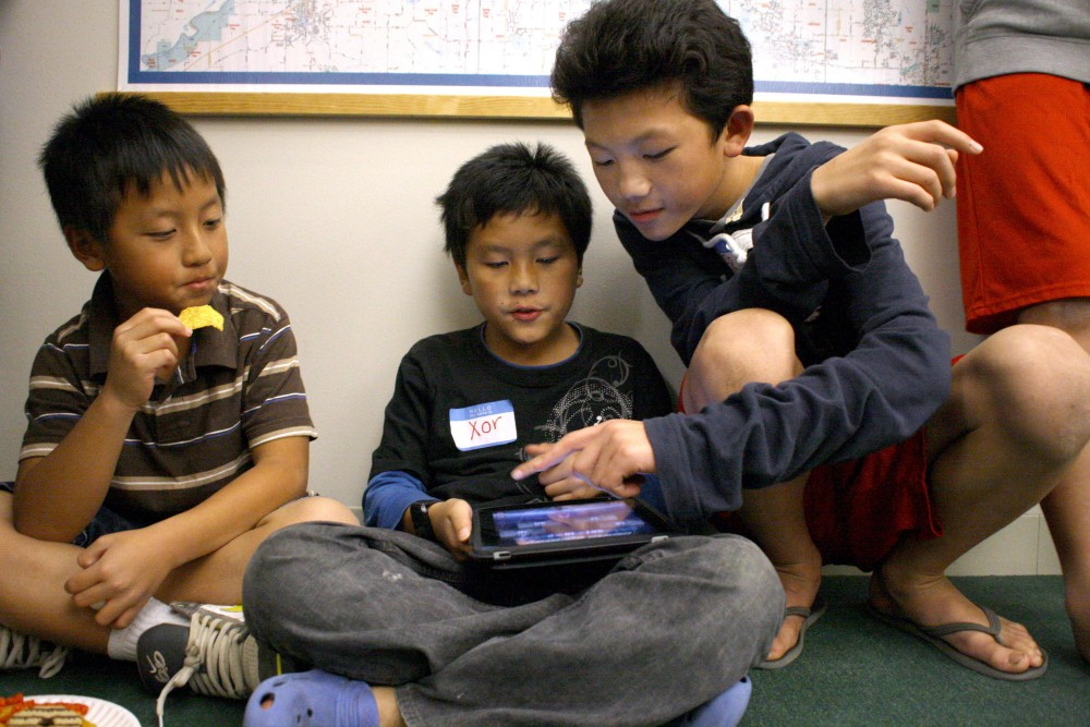 Grade school students, from left to right, Meng Lee, Xor Vue and Ser Yang play math games on an iPad during a snack break Sunday at the Center for Urban and Regional Affairs at the Hubert Humphrey Center in Minneapolis. Many local grade school students come to the Sunday Tutoring Program to get help with homework from University of Minnesota students.