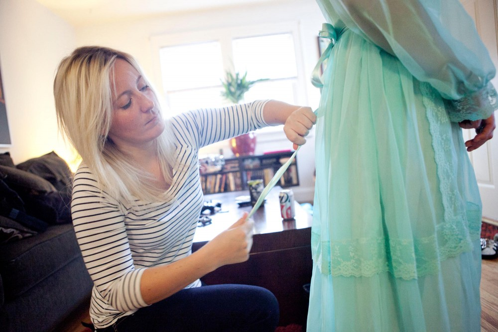 Designer Abby Christenson fixes the ribbon of one of her dress designs that will be in the Vogue/ Trash Fashion Show in her home in South Minneapolis Wednesday afternoon.