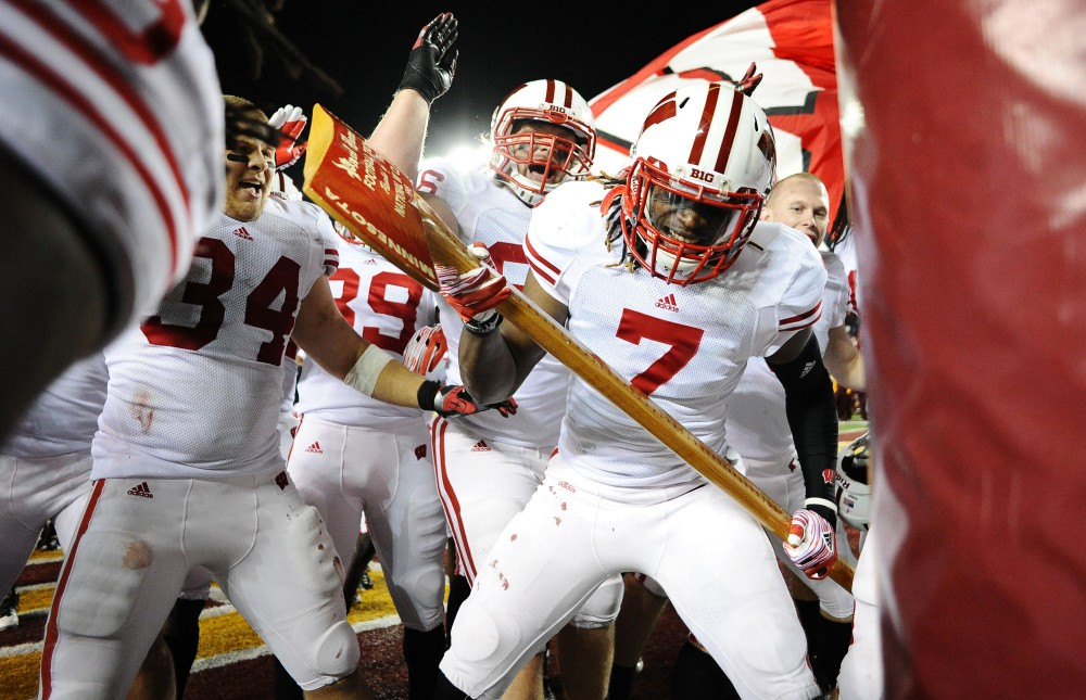 Wisconsin defensive back Aaron Henry attacks a goal post with Paul Bunyan's Axe after defeating Minnesota 42-13 Saturday at TCF Bank Stadium.