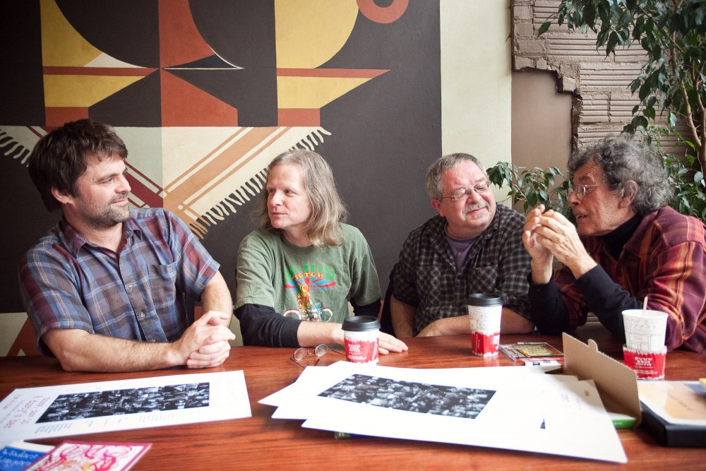 Jeffrey Skemp, left, Scott Vesch, middle left, Kevin Brixius, middle right, and Lynn Gray, right, talk about their experiences with live poetry readings Sunday afternoon at Dunn Bros.