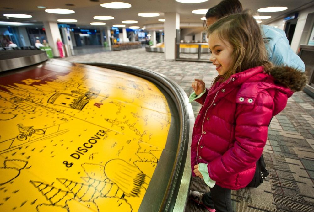 7-year-old Isabella Konat looks at a Driven to Discover advertisement that caught her eye Tuesday in the baggage claim area at the Minneapolis-St. Paul International Airport in St. Paul.