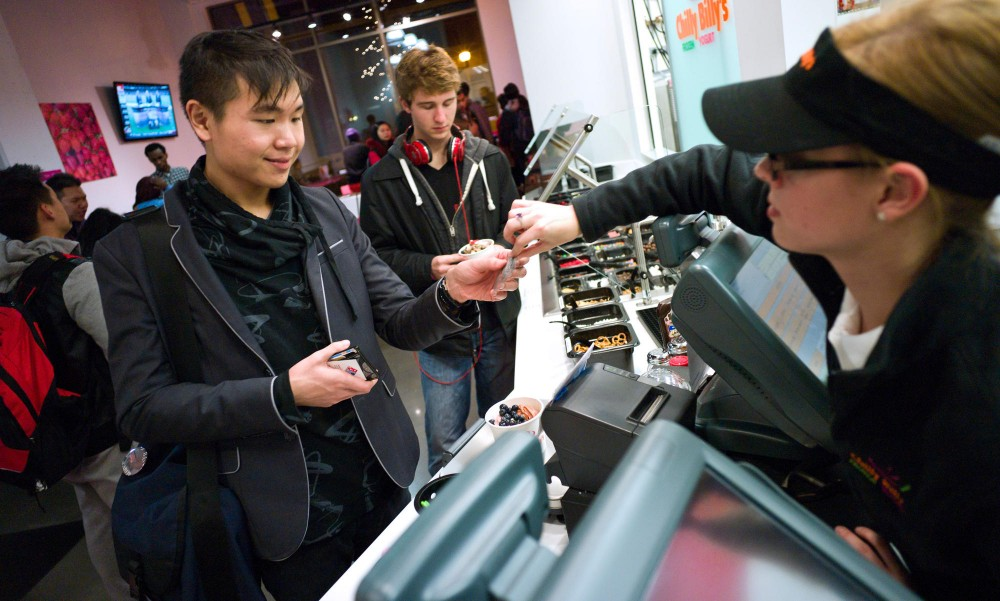 Pi Delta Psi senior Patrick Lin pays for a frozen yogurt at Chilly Billy's on Monday in Dinkytown.