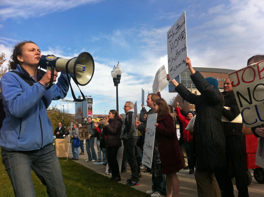 Deputy Organizing & Training Director of TakeAction Minnesota Elizabeth Lienesch leads a protest outside of McNamara Alumni Center Tuesday on East Bank. The protest was meant to pressure Wells Fargo CEO Jon Stumpf into changing educational loaning policies.