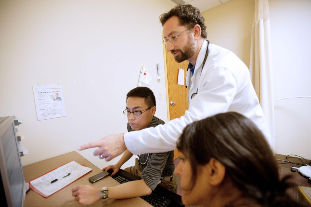 Second-year resident Victor Yam, left, discusses with medical doctor David Satin, right, which medication is best fitted for a patient Thursday at Smiley's Clinic.