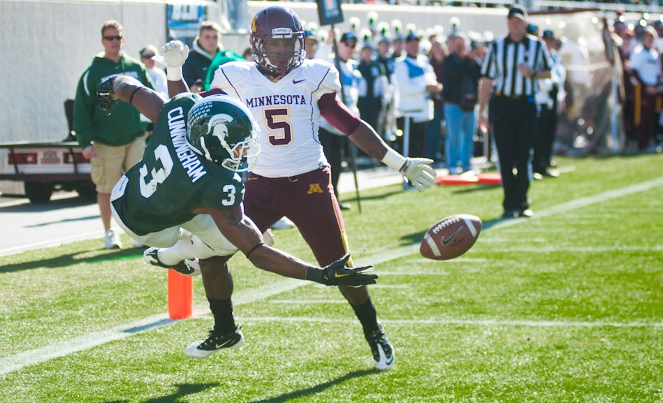 Michigan State wide receiver B.J. Cunningham attempts to catch the ball for a touchdown under the pressure of Gophers defensive back Johnny Johnson Saturday at the Spartan Stadium.